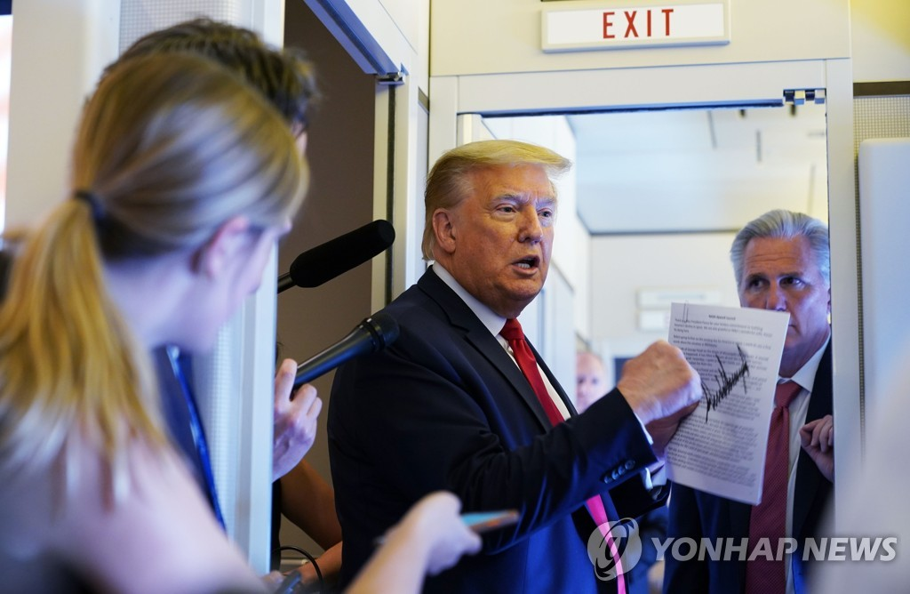 This AFP photo shows U.S. President Donald Trump speaking to reporters aboard Air Force One en route to Andrews Air Force Base, Maryland, on May 30, 2020. (Yonhap)