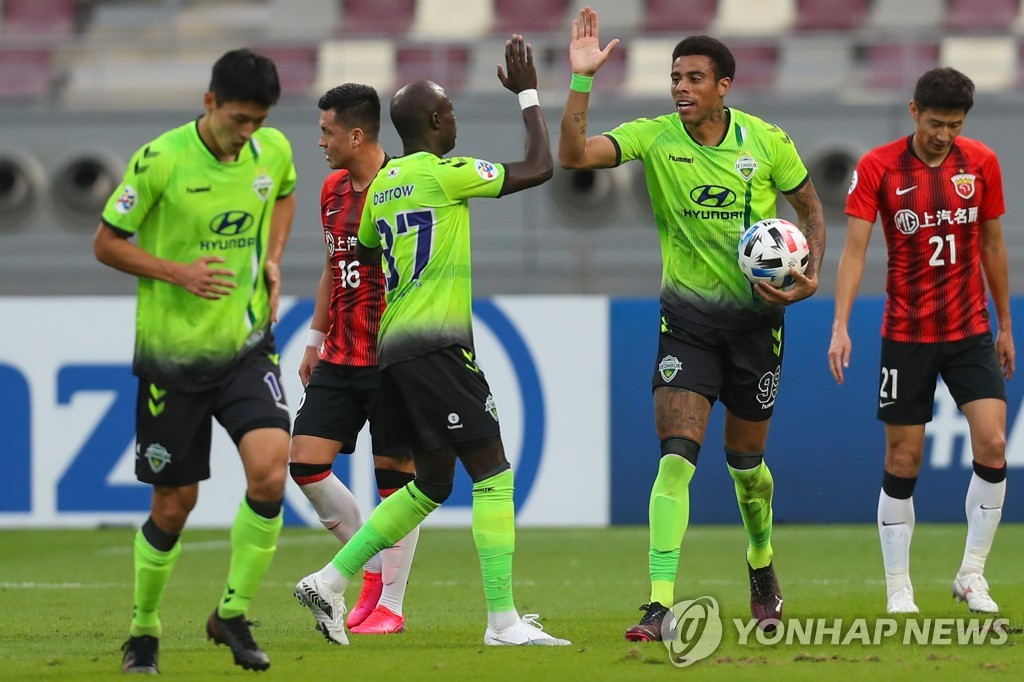 In this AFP photo, Gustavo of Jeonbuk Hyundai Motors (2nd from R) celebrates with teammate Mo Barrow after scoring a goal against Shanghai SIPG during their Group H match at the Asian Football Confederation Champions League at Khalifa International Stadium in Doha on Nov. 22, 2020. (Yonhap)