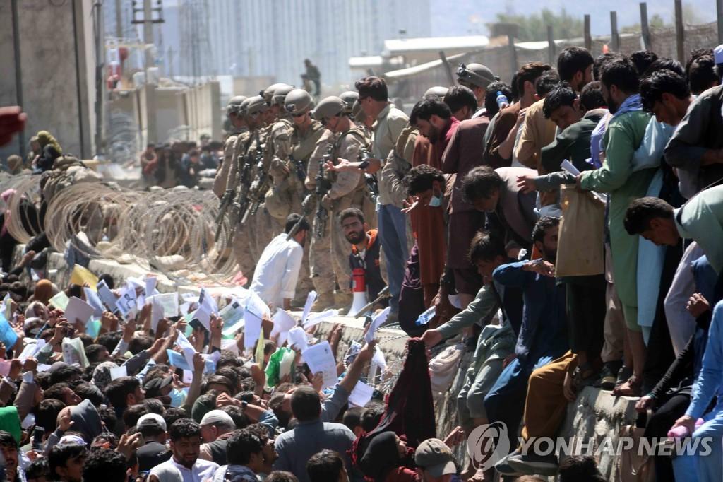 대피작전 대상자임을 증명하는 문서를 들고 카불공항으로 향하는 아프간 현지 협력자들. 미군 철수 뒤 극단주의 무장정파 탈레반이 아프간을 장악하면서 유일한 탈출구인 카불공항에서는 피란인파가 몰려 대혼란이 지속되고 있다. [EPA=연합뉴스]