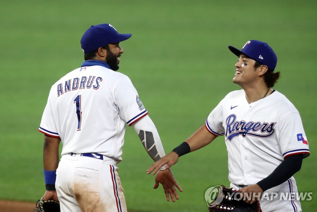 In this Getty Images file photo from July 29, 2020, Choo Shin-soo of the Texas Rangers (R) celebrates a 7-4 win over the Arizona Diamondbacks with his teammate Elvis Andrus at Globe Life Field in Arlington, Texas. (Yonhap)