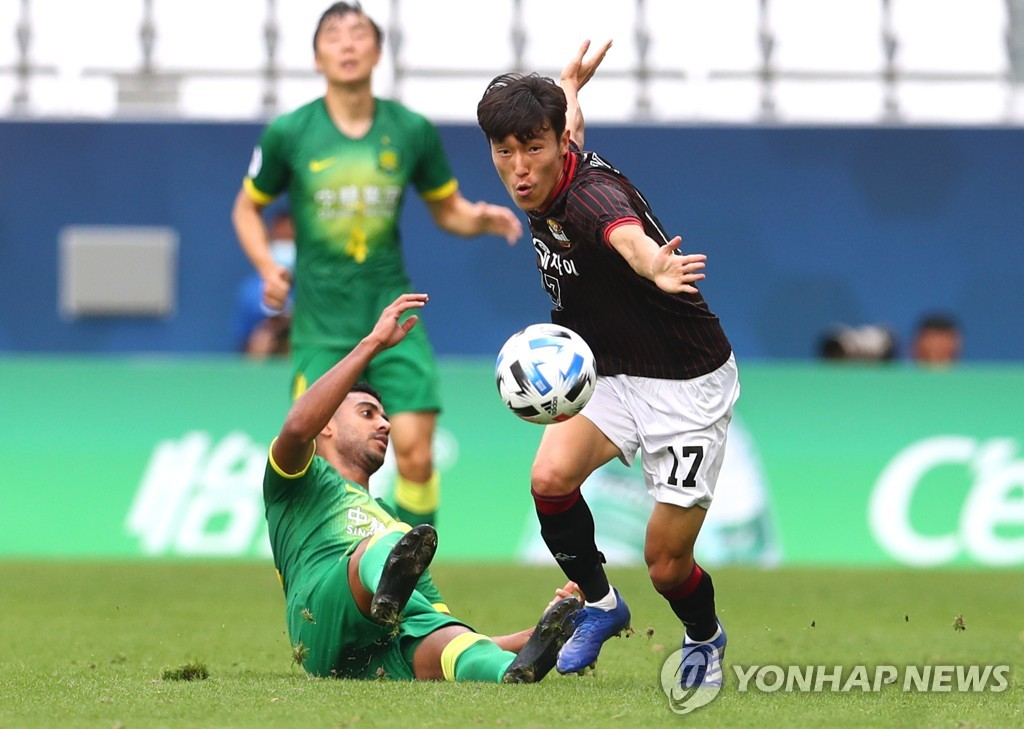 In this Reuters photo, Kim Jin-ya of FC Seoul (R) battles Alan Carvalho of Beijing Guoan for the ball during their Group E match at the Asian Football Confederation Champions League at Education City Stadium in Al Rayyan, Qatar, on Nov. 21, 2020. (Yonhap)
