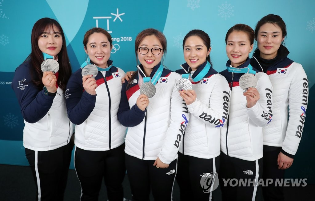 This file photo taken Feb. 25, 2018, shows the South Korean women's curling team posing for a group photo after winning the silver medal at the 2018 PyeongChang Olympics. From right are head coach Kim Min-jung, Kim Eun-jung, Kim Kyeong-ae, Kim Seon-yeong, Kim Yeong-mi and Kim Cho-hee. (Yonhap)