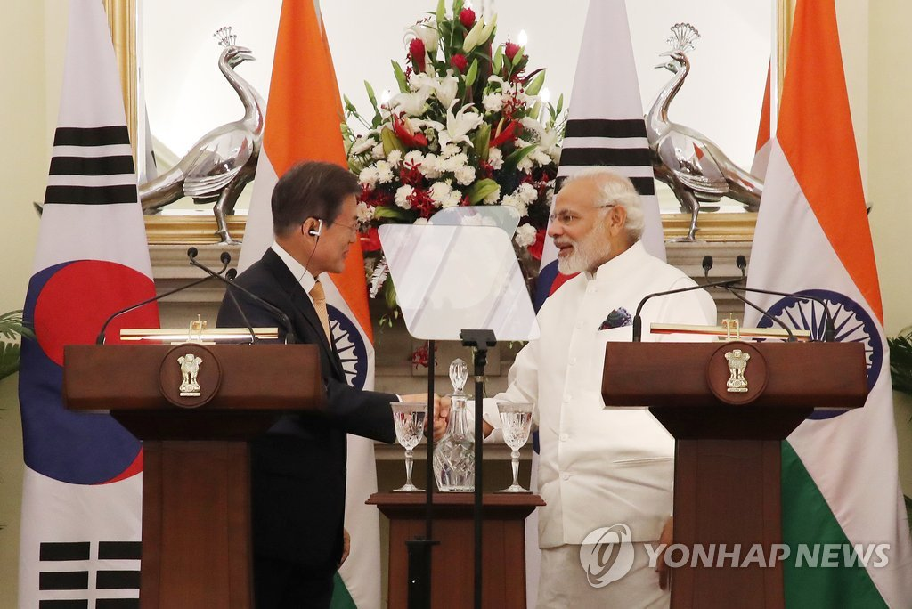 In the photo taken July 10, 2018, South Korean President Moon Jae-in (L) and Indian Prime Minister Narendra Modi shakes hands after holding a joint press conference on the outcome of their bilateral summit held in New Delhi during Moon's state visit to India. (Yonhap)