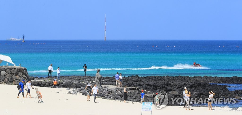In this file photo taken on July 11, 2018, tourists walk on Gwakji Beach on the southern resort island of Jeju. (Yonhap)