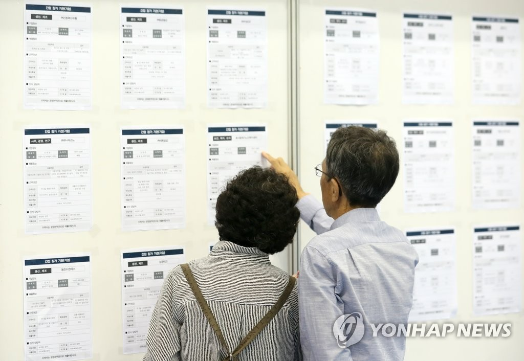 This photo, taken on Sept. 19, 2018, shows senior job seekers looking at a bulletin board containing information on job posts at a job fair held in the southeastern port city of Busan. (Yonhap)