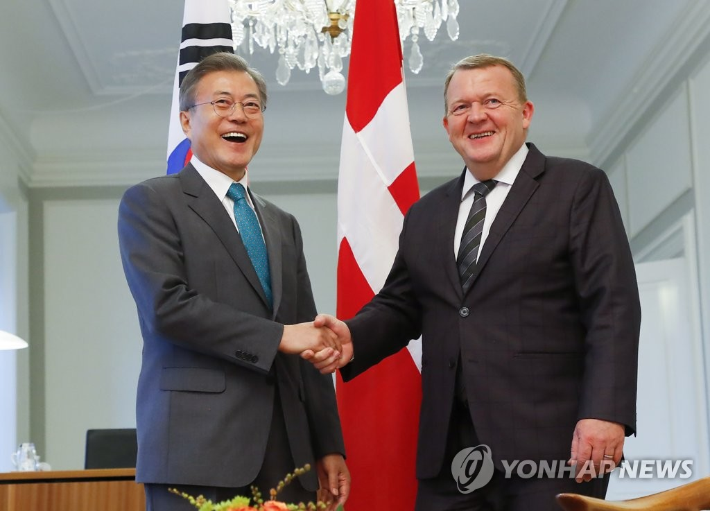 South Korean President Moon Jae-in (L) and Danish Prime Minister Lars Lokke Rasmussen shake hands before holding a bilateral summit in Copenhagen on Oct. 20, 2018. (Yonhap)