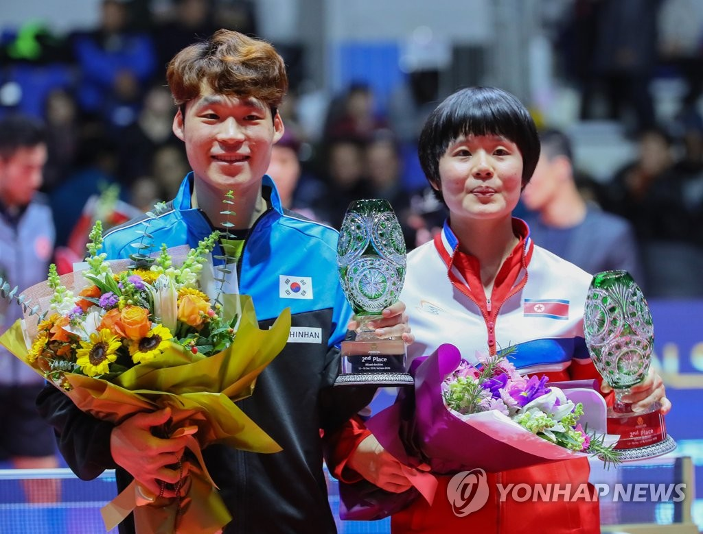 In this file photo from Dec. 15, 2018, Jang Woo-jin of South Korea (L) and Cha Hyo-sim of North Korea hold up their second-place trophies in the mixed doubles during the awards ceremony at the International Table Tennis Federation World Tour Grand Finals at Namdong Gymnasium in Incheon, 40 kilometers west of Seoul. (Yonhap)