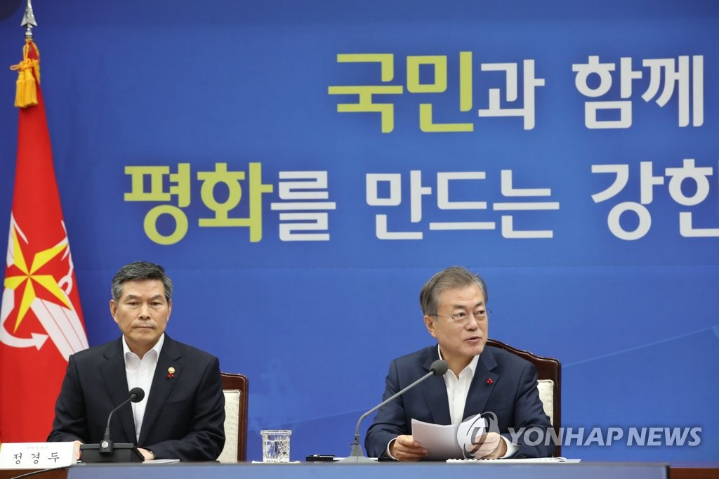 President Moon Jae-in (R) and Defense Minister Jeong Kyeong-doo attend the defense ministry's briefing on its policy plans for 2019 at the ministry building in Seoul on Dec. 20, 2018. (Yonhap)