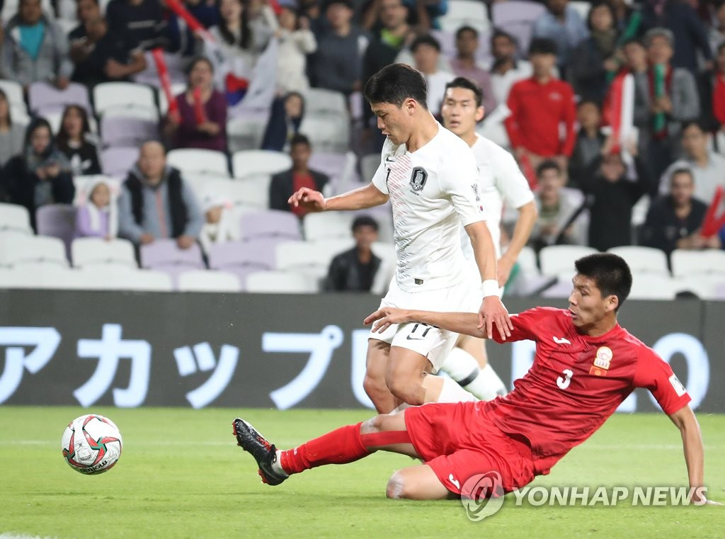 Hwang Hee-chan of South Korea (L) is challenged by Tamirlan Kozubaev of Kyrgyzstan during the teams' Group C match at the Asian Football Confederation Asian Cup at Hazza Bin Zayed Stadium in Al Ain, the United Arab Emirates, on Jan. 11, 2019. (Yonhap)