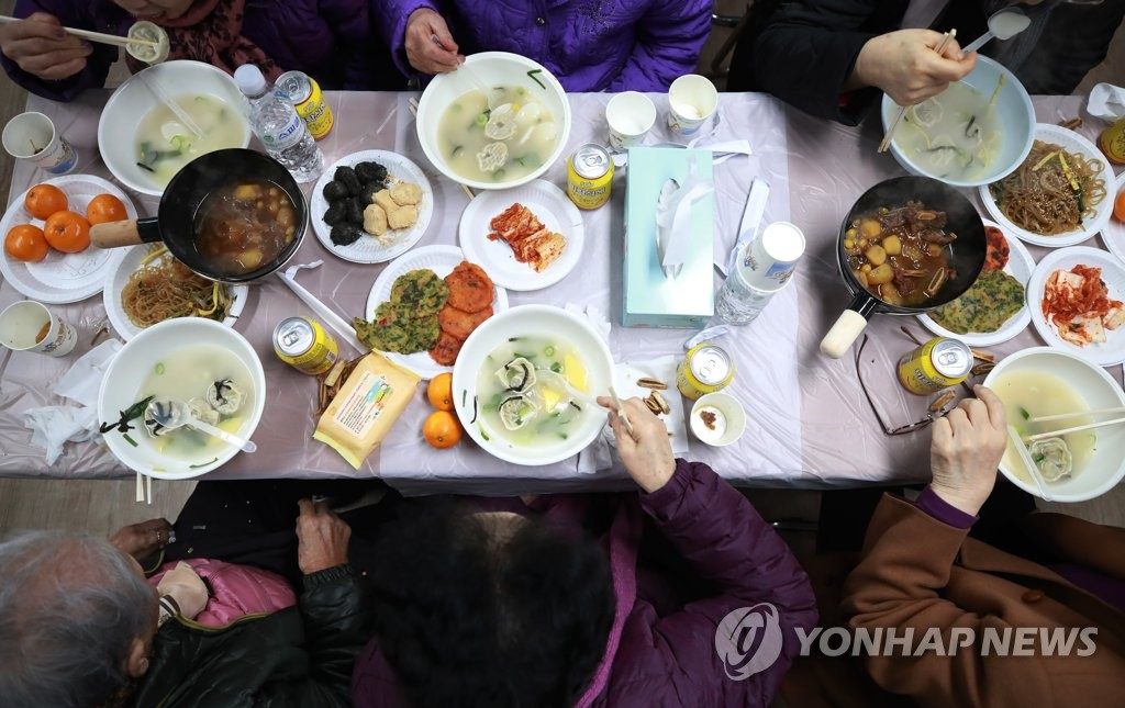 "Elderly people enjoying a traditional feast of ""tteokguk"" soup in Seoul. (Yonhap)"