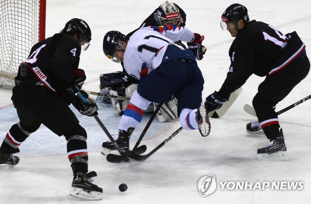 Kim Ki-sung of South Korea (C) fights for the loose puck against Japan during the teams' final match at the Legacy Cup men's hockey tournament at Gangneung Hockey Centre in Gangneung, 230 kilometers east of Seoul, on Feb. 8, 2019. (Yonhap)