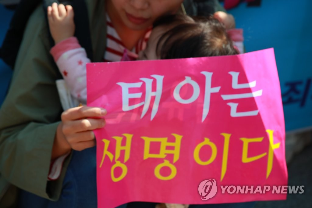 "A woman with a baby holds a sign that reads ""A fetus is a life,"" during an anti-abortion rally held in Seoul ahead of the Constitutional Court's ruling on April 11, 2019. (Yonhap)"