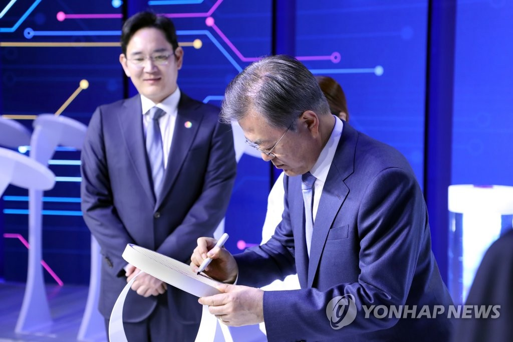 This file photo, taken April 30, 2019, shows President Moon Jae-in (R) signing a newly developed chip produced at a Samsung Electronics factory in Hwaseong. Samsung's leader Lee Jae-yong was standing next to him. (Yonhap)