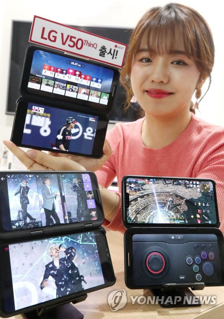A model holds up an LG V50 ThinQ at a shop in Seoul on May 10 2019. (Yonhap)