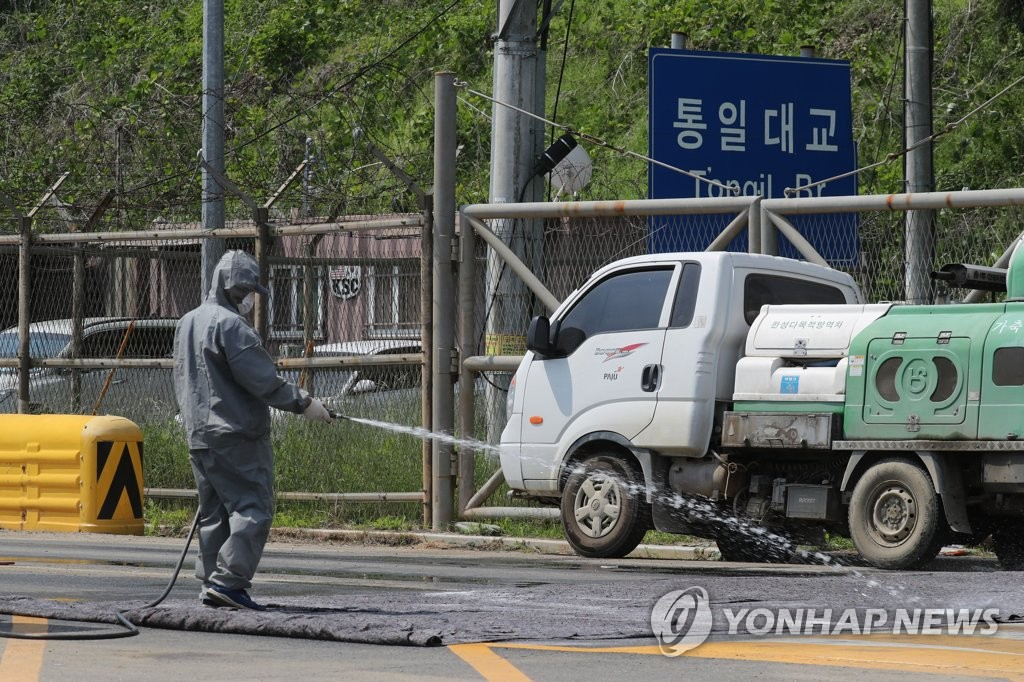 A sanitation official disinfects a road near the Tongil Bridge in Paju, north of Seoul, on June 3, 2019, in an effort to prevent African swine fever from hitting the region following its outbreak in North Korea. (Yonhap)