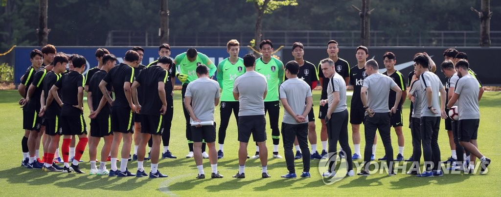 Members of the South Korean men's national football team and their coaches (in grey) form a huddle before practice at the National Football Center in Paju, Gyeonggi Province, on June 3, 2019. (Yonhap)
