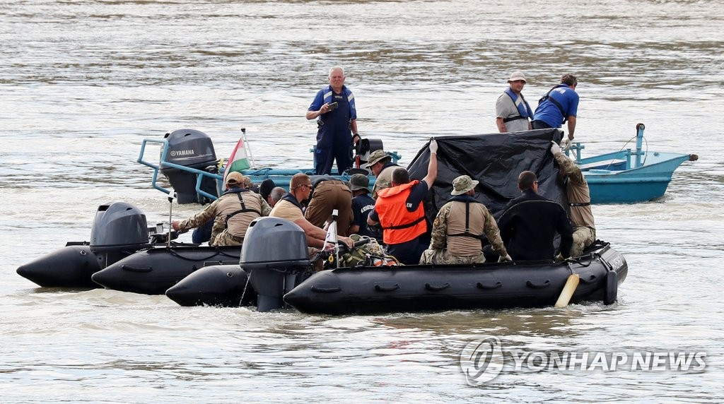 Hungarian rescue workers retrieve a body believed to be a South Korean victim of a deadly boat sinking from underwater in the Danube River near the Margit Bridge in Budapest on June 3, 2019. (Yonhap)