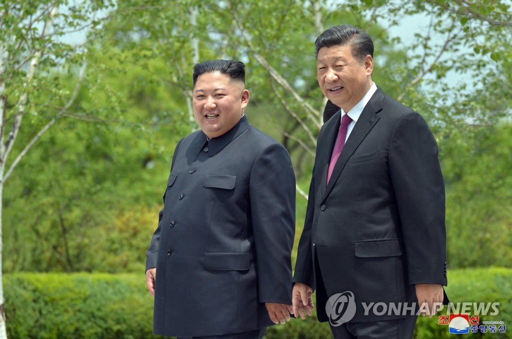 In this file photo taken June 21, 2019, and released by North Korea's official Korean Central News Agency, Chinese President Xi Jinping (R) and North Korean leader Kim Jong-un take a walk at the Kumsusan State Guesthouse in Pyongyang. (For Use Only in the Republic of Korea. No Redistribution) (Yonhap)
