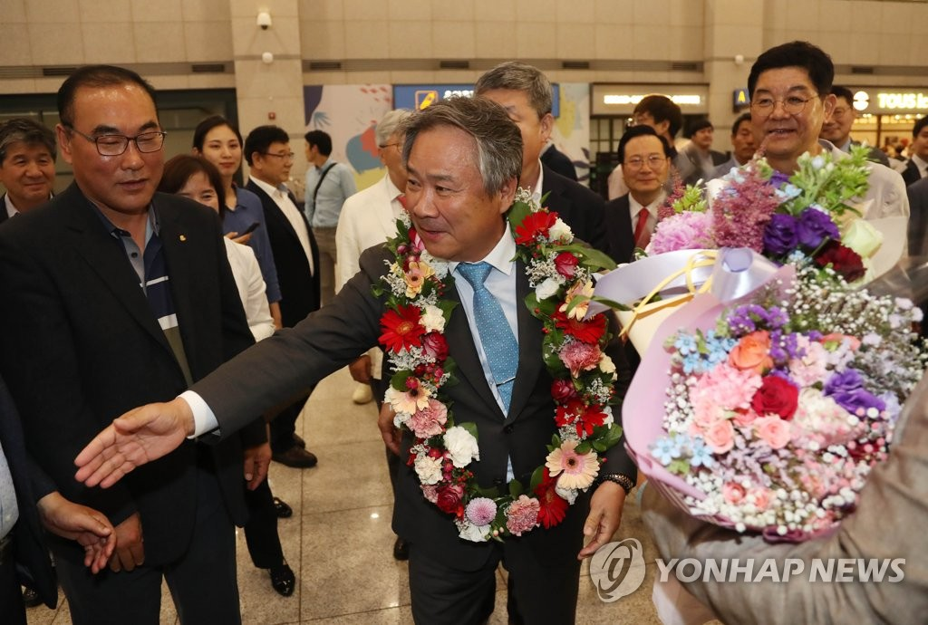 Lee Kee-heung (C), president of the Korean Sport & Olympic Committee (KSOC), is greeted by South Korean sports officials at Incheon International Airport, west of Seoul, on June 28, 2019, following his election as a member of the International Olympic Committee. (Yonhap)
