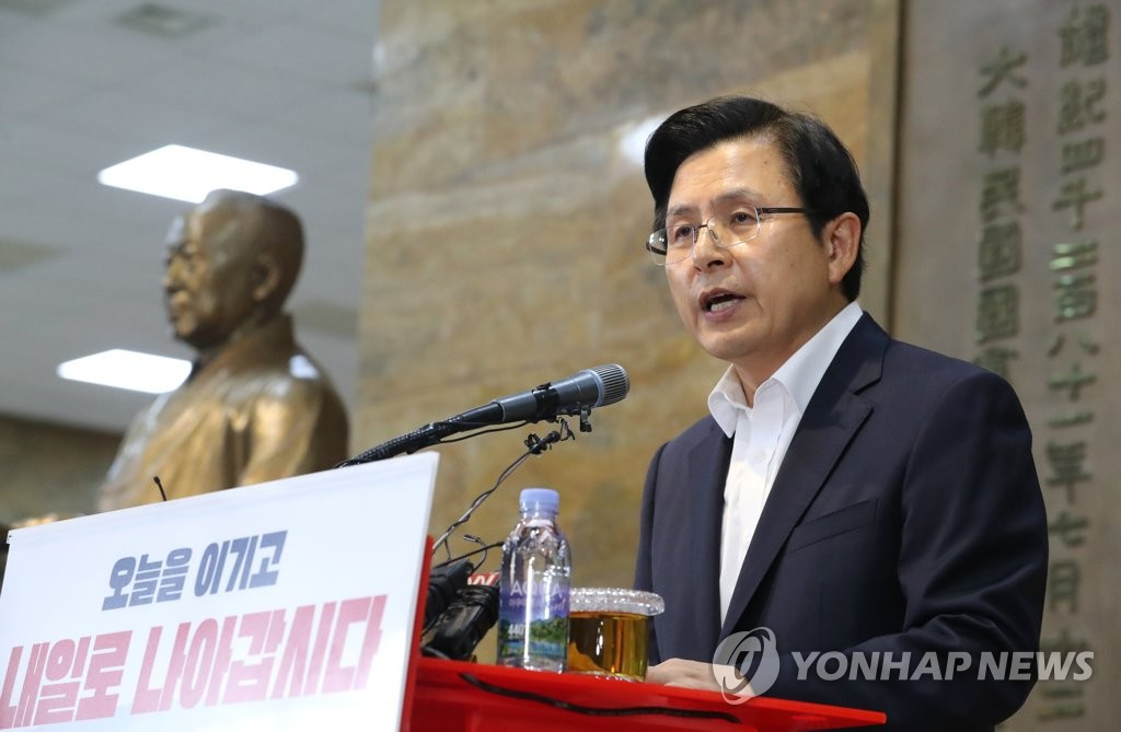 Hwang Kyo-ahn, chairman of the main opposition Liberty Korea Party, reads a public statement on the occasion of the Aug. 15 Liberation Day beside a statue of Rhee Syng-man, South Korea's first president, at the National Assembly on Aug. 14, 2019. (Yonhap)