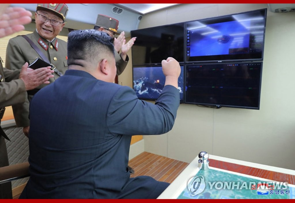 "This photo, released by North Korea's Central News Agency on Aug. 17, 2019, shows North Korean leader Kim Jong-un (C) reacting to the country's test of a ""new weapon"" a day earlier. (For Use Only in the Republic of Korea. No Redistribution) (Yonhap)"