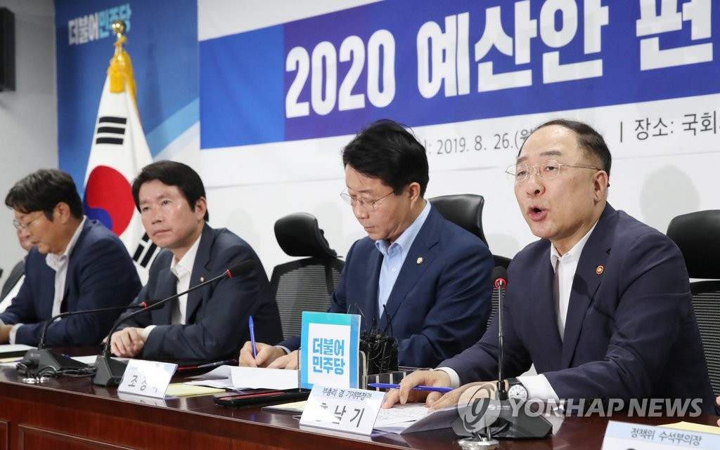 Hong Nam-ki (R), the minister of economy and finance, speaks in a meeting with lawmakers of the ruling Democratic Party for consultations on next year's budget at the parliament on Aug. 26, 2019. (Yonhap)