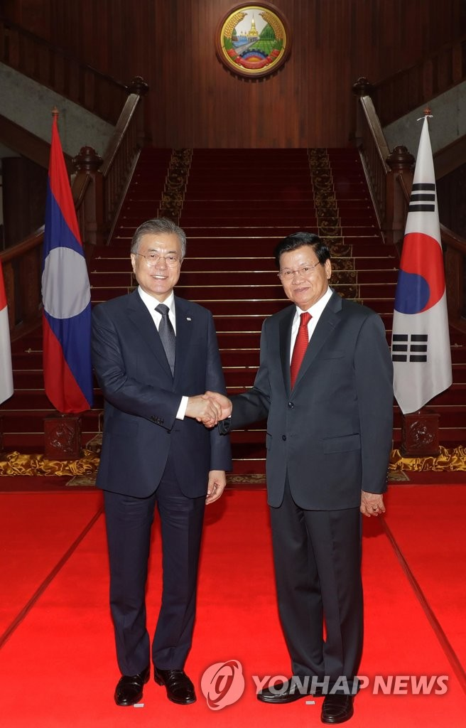 South Korean President Moon Jae-in and Laotian Prime Minister Thongloun Sisoulith shake hands during a meeting in Vientiane on Sept. 5, 2019. (Yonhap)