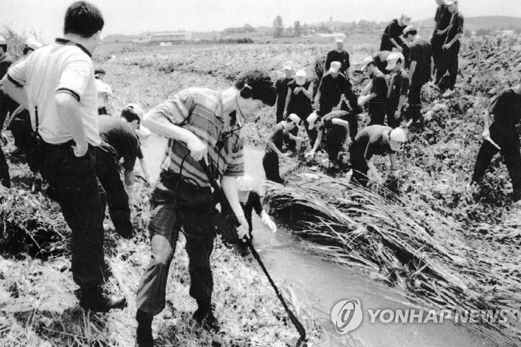 This file photo shows police officers investigating serial murders in Hwaseong in July, 1993. (Yonhap)