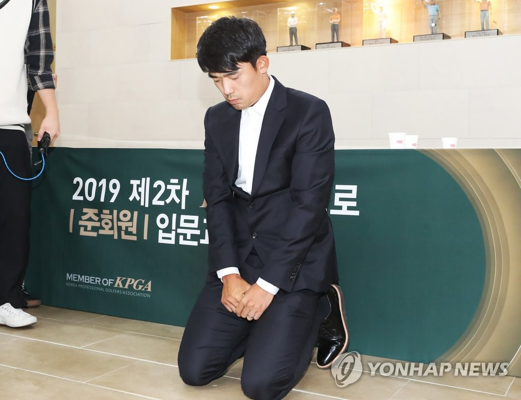 In this file photo from Oct. 1, 2019, South Korean golfer Kim Bi-o apologizes to fans on his knees after attending a disciplinary hearing at the Korea Professional Golfers' Association headquarters in Seongnam, south of Seoul. Kim was initially suspended for three years after raising his middle finger at the crowd over cellphone camera noise during a recent Korean Tour event, but the penalty was reduced to one year on Oct. 23, 2019. (Yonhap)