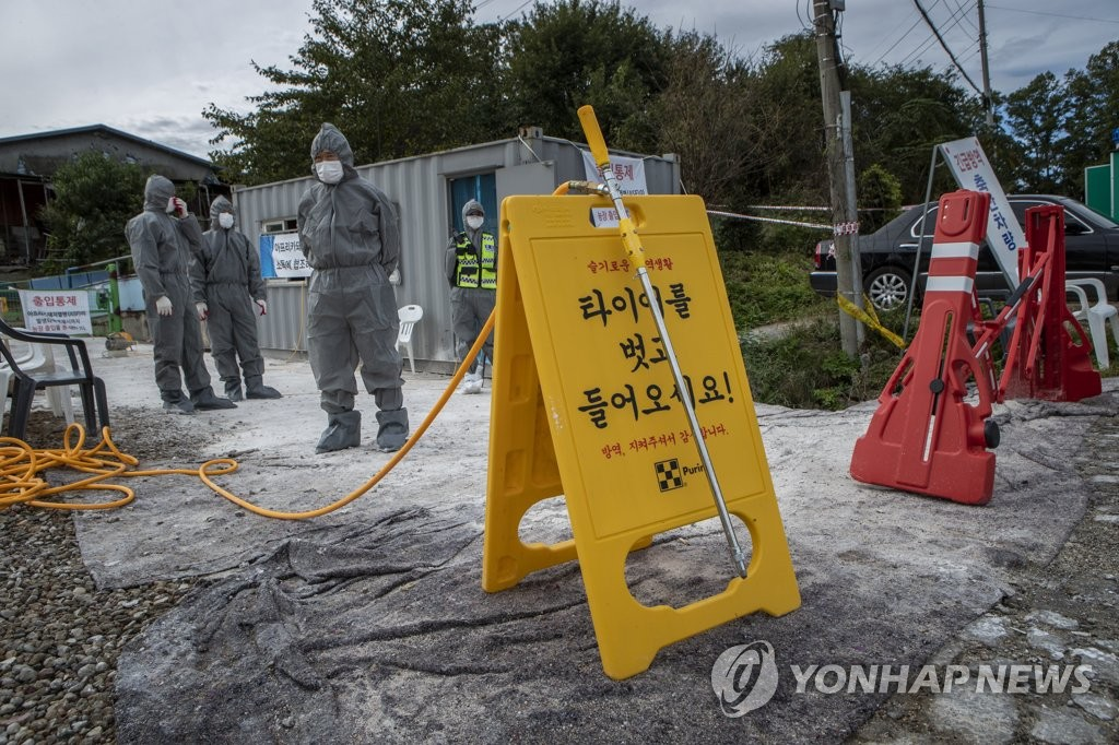 Quarantine officials set up a sign at a pig farm in Paju, north of Seoul, on Oct. 3, 2019, as they carry out disinfection operations against African swine fever. (Yonhap)