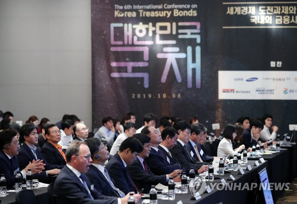South Korean Finance Minister Hong Nam-ki (5th from L, front row) and other participants listen to comments by panelists at an international conference on Korea Treasury bonds at the Conrad Hotel in western Seoul on Oct. 8, 2019. (Yonhap)