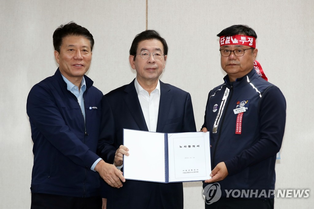 Seoul Metro CEO Kim Tae-ho (L), Seoul Mayor Park Won-soon (C) and Seoul Metro labor union leader Yoon Byung-beom pose with a document on the agreement at the company's headquarters in Seoul on Oct. 16, 2019. (Yonhap)