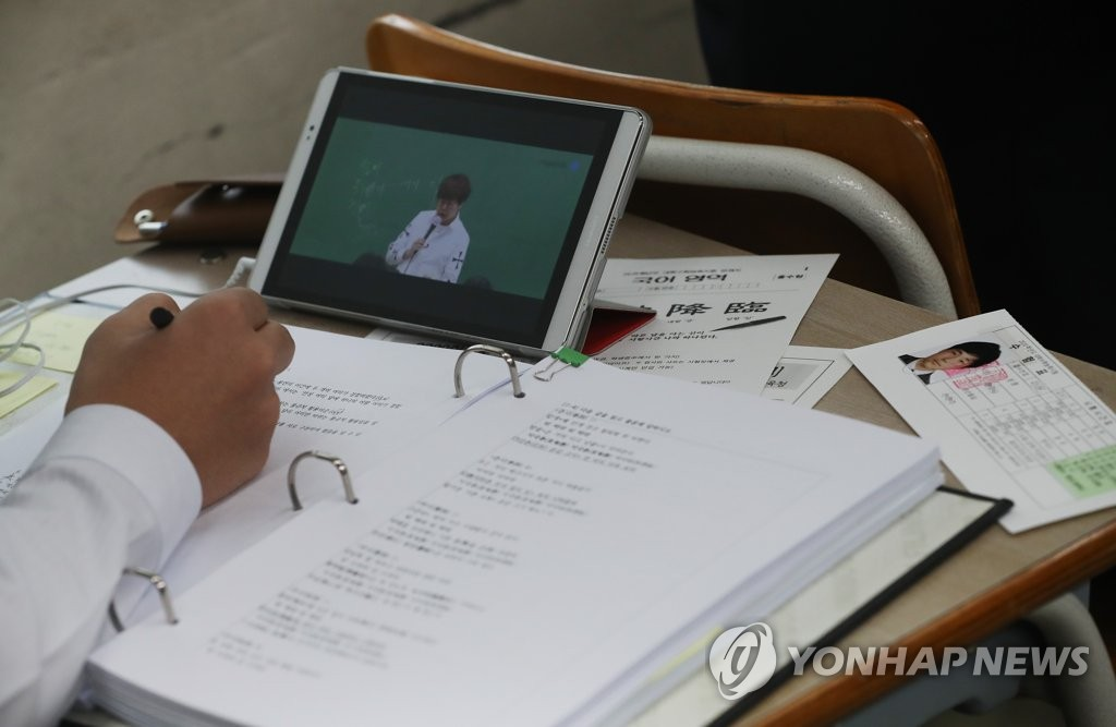 In this file photo, taken Nov. 13, 2019, a senior takes an internet class after receiving his test identification slip from his homeroom teacher at Yongsan High School in Seoul, one day ahead of an annual state-administered scholastic aptitude test. (Yonhap)