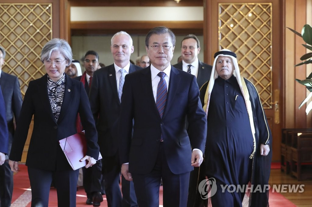 President Moon Jae-in (C) walks toward a meeting room with Foreign Minister Kang Kyung-wha (L) and new ambassadors to South Korea after receiving their credentials at Cheong Wa Dae in Seoul on Oct. 16, 2020. (Yonhap)