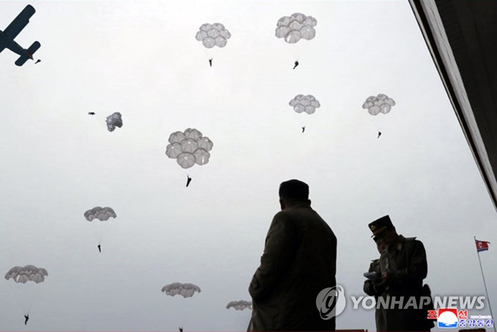 North Korean leader Kim Jong-un (L) watches sharpshooters of the North's Air and Anti-Aircraft Force conduct an airborne landing training, in this photo provided by the Korean Central News Agency on Nov. 18, 2019. (For Use Only in the Republic of Korea. No Redistribution) (Yonhap)