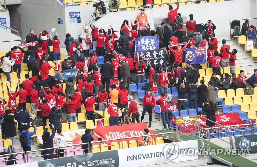 Fans of Hong Kong men's national football team stand with their backs turned during the Chinese national anthem ahead of their team's match against China at the East Asian Football Federation (EAFF) E-1 Football Championship at Busan Asiad Main Stadium in Busan, 450 kilometers southeast of Seoul, on Dec. 18, 2019. (Yonhap)