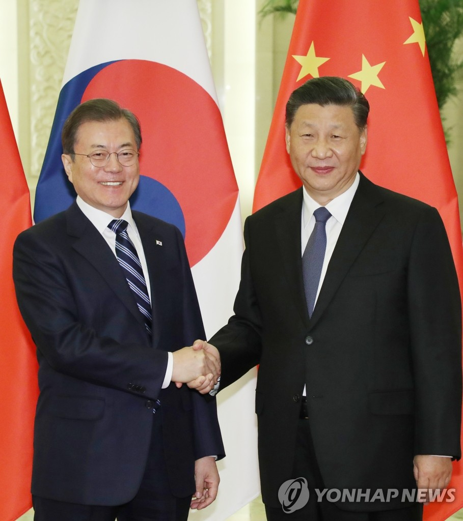 South Korean President Moon Jae-in (L) shakes hands with Chinese President Xi Jinping in their summit at the Great Hall of the People in Beijing on Dec. 23, 2019. (Yonhap)