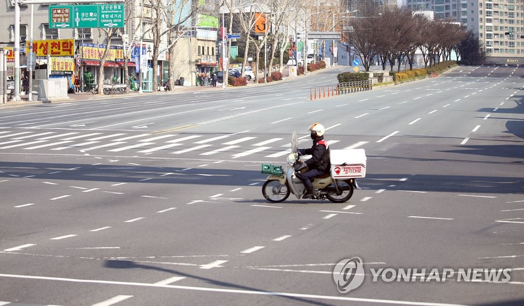 A motorcycle drives through an empty road in Daegu on Feb. 20, 2020. (Yonhap)