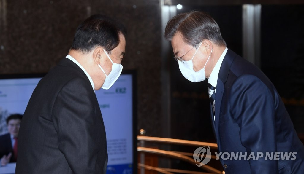 President Moon Jae-in (R) is greeted by National Assembly Speaker Moon Hee-sang, both wearing face masks, at the parliamentary building in western Seoul on Feb. 28, 2020. (Yonhap)