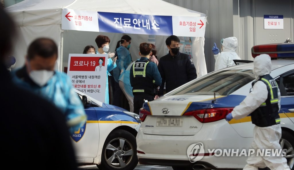 Police and hospital officials are seen at Inje University Seoul Paik Hospital in central Seoul on March 9, 2020. The hospital was closed after a patient from Daegu was diagnosed with COVID-19. (Yonhap)