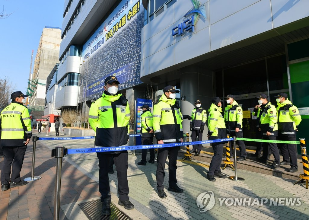 Police guard the entrance of the Shincheonji Church of Jesus building in the southern city of Daegu after district prosecutors and Daegu city officials entered the building as part of their probe into the church in connection with a coronavirus infection cluster, in this photo provided by Daegu city on March 17, 2020. (PHOTO NOT FOR SALE) (Yonhap)