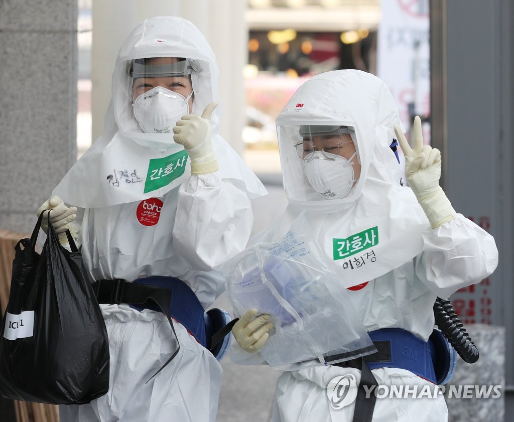 Medical workers with protective gear gesture as they arrive for a shift at Dongsan Hospital in the virus-hit city of Daegu on March 25, 2020. (Yonhap)