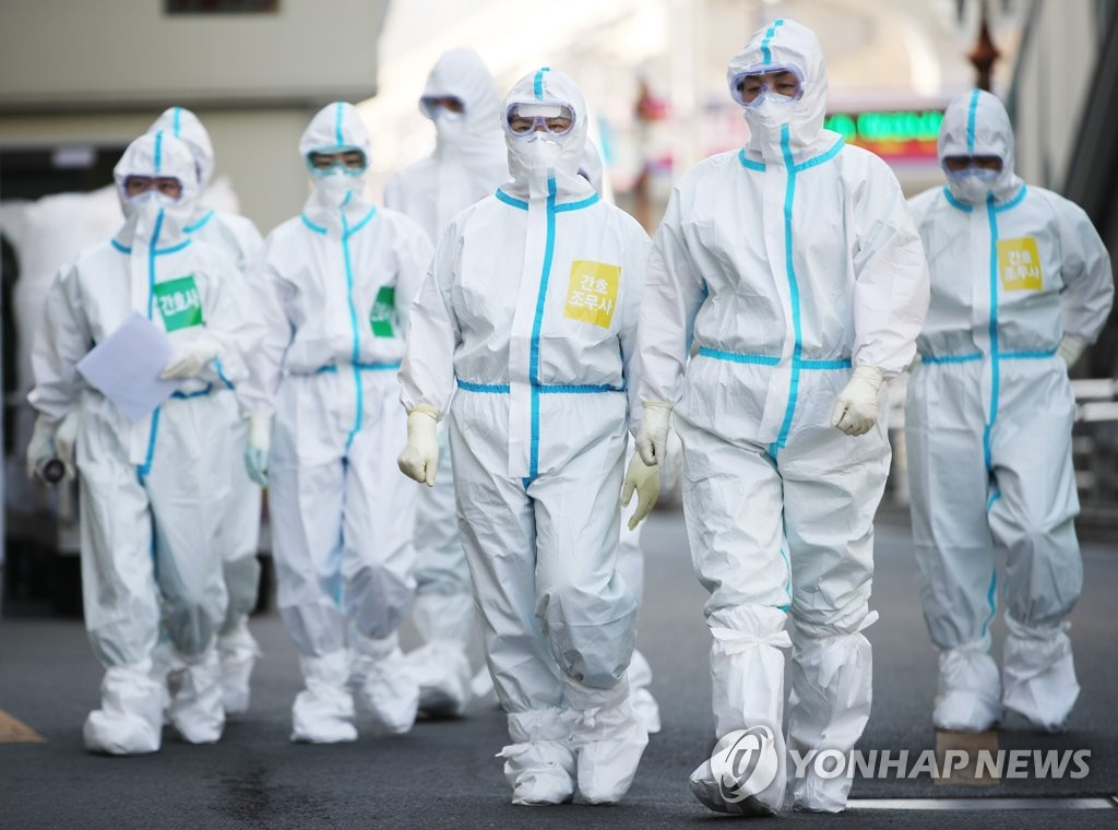 Health workers in protective suits enter Keimyung University Dongsan Hospital in Daegu on March 31, 2020. (Yonhap)