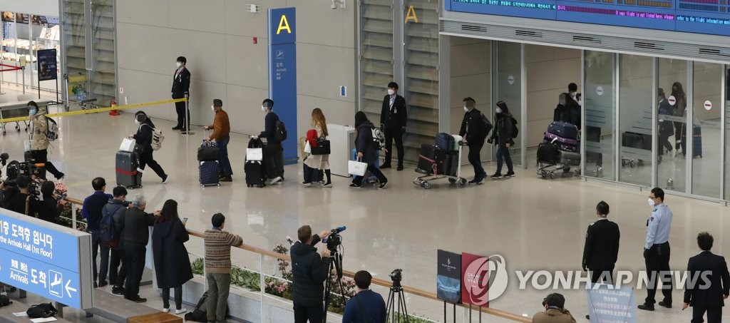 South Koreans who arrived on a chartered flight from Italy head to a virus screening area at Incheon International Airport, west of Seoul, on April 1, 2020. (Yonhap)