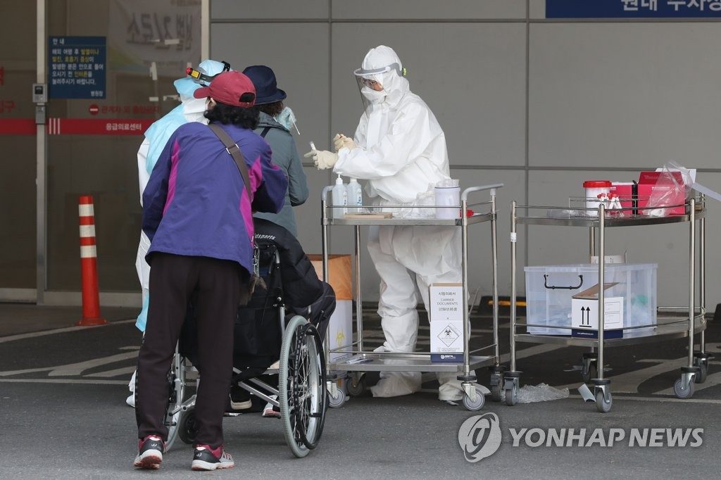 This photo taken on April 2, 2020, shows a health worker checking visitors at St. Mary's Hospital in Uijeongbu, north of Seoul, where group infection of the new coronavirus has been reported. (Yonhap)