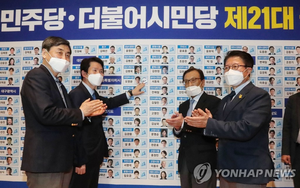 This photo, taken on April 15, 2020, shows officials of the Democratic Party and its satellite party posing in front of a board at the National Assembly in Seoul showing seats the parties have secured in the general elections. (Yonhap)