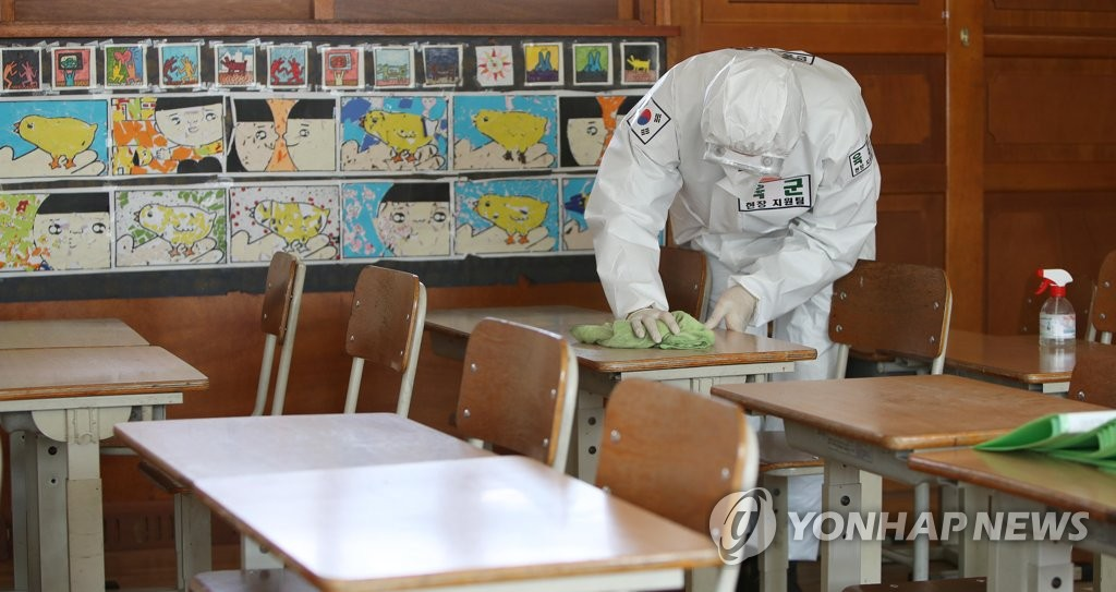 A soldier disinfects a desk at an elementary school in the southern city of Daegu on May 1, 2020. (Yonhap)