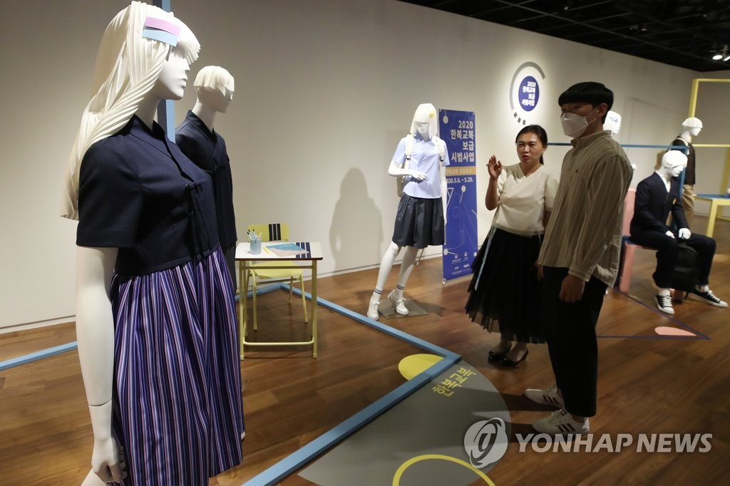 "In this file photo, employees of the Hanbok Advancement Center check displays of school uniforms that use modern designs based on ""hanbok,"" traditional Korean clothes, at a gallery in Seoul on May 7, 2020. The exhibition is a joint project of the culture and education ministries to promote the use of hanbok in schools. (Yonhap)"