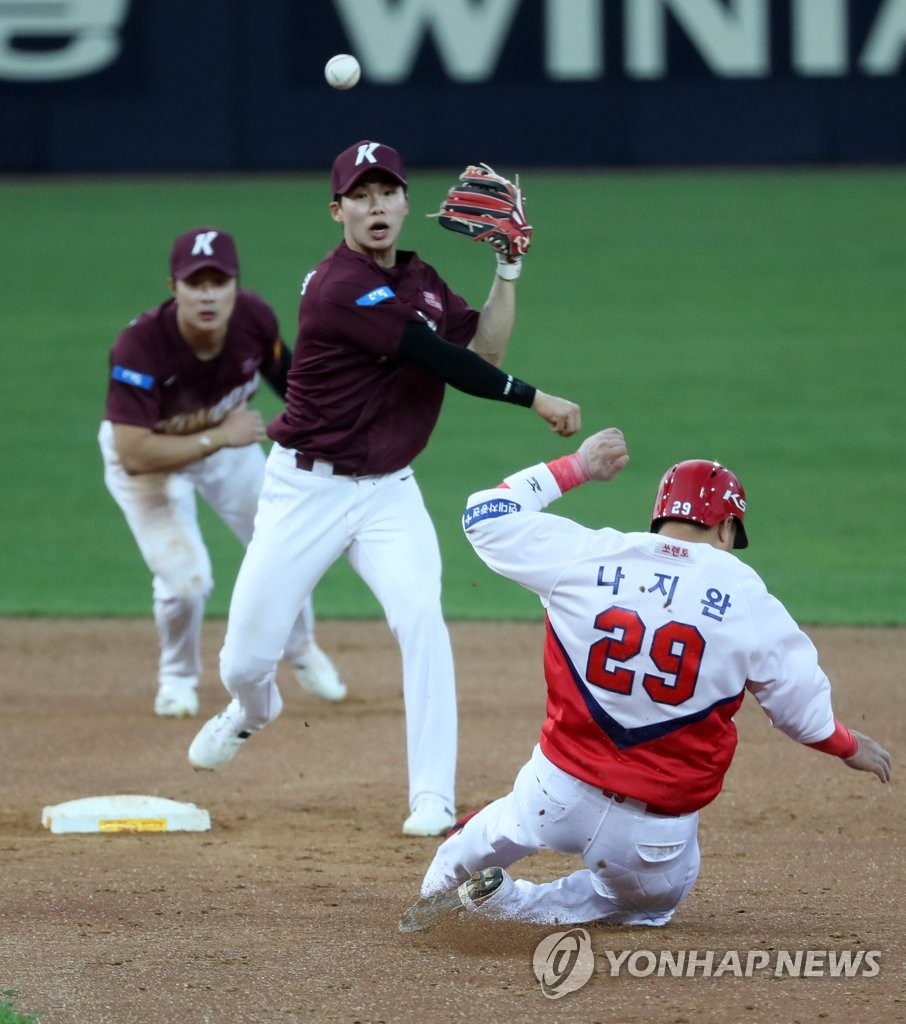 In this file photo from May 5, 2020, Kiwoom Heroes' second baseman Kim Hye-seong (C) throws to first to complete a double play against the Kia Tigers in a Korea Baseball Organization regular season game at Gwangju-Kia Champions Field in Gwangju, 330 kilometers south of Seoul. (Yonhap)