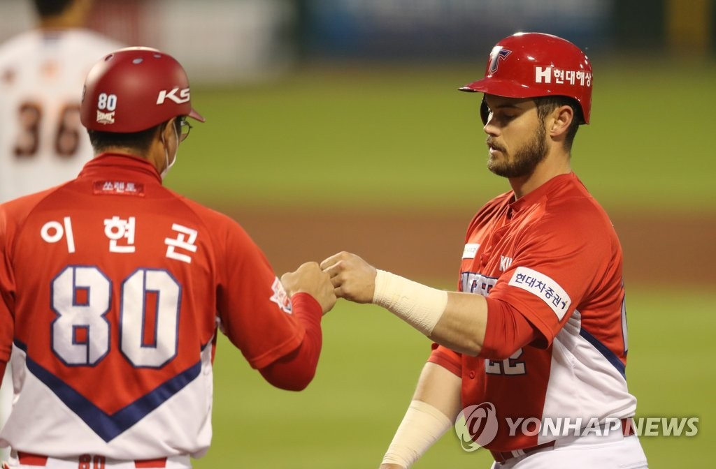 Preston Tucker of the Kia Tigers (R) bumps fists with first base coach Lee Hyun-gon after a single against the Hanwha Eagles during a Korea Baseball Organization regular season game at Hanwha Life Eagles Park in Daejeon, 160 kilometers south of Seoul, on May 14, 2020. (Yonhap)